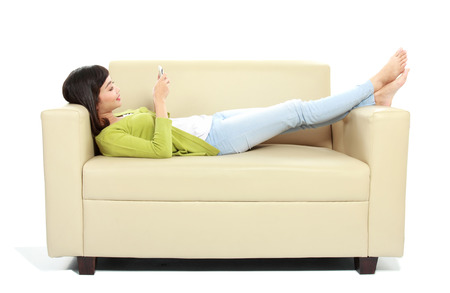 Young girl using her cellphone on the couch over white  photo