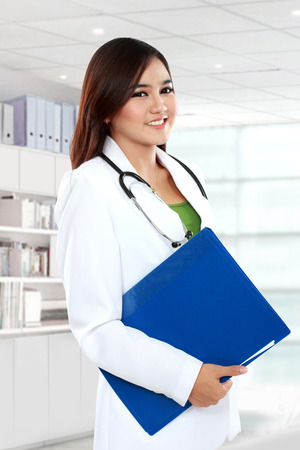 Attractive female doctor in lab coat holding clipboard at hospital photo