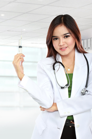 asian medical: Portrait of asian female doctors wearing a white coat and stethoscope posing with syringe Stock Photo