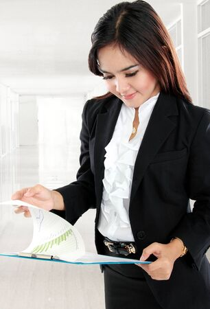 Portrait of busy businesswoman open paper and holding clipboard in her office photo