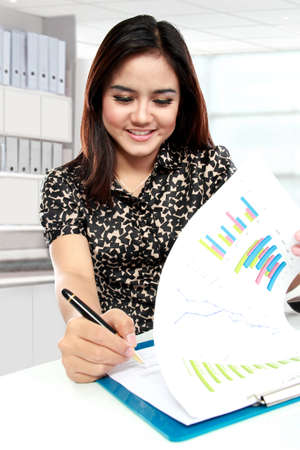 Portrait of young businesswoman working with papers in office photo