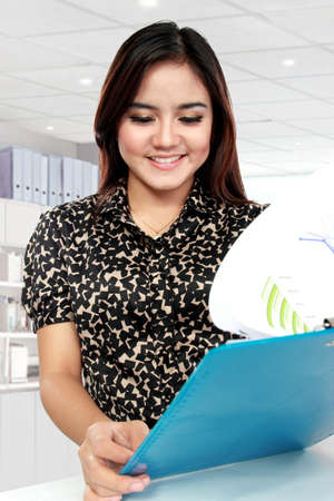 Portrait of businesswoman working with papers in office photo