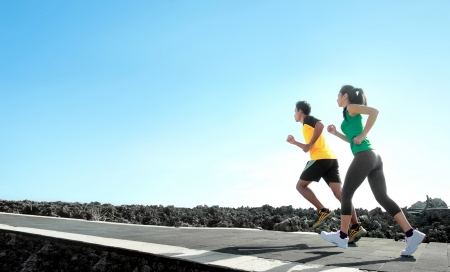 hacer footing: Deporte - el par asi�tico correr al aire libre que hace ejercicio Foto de archivo