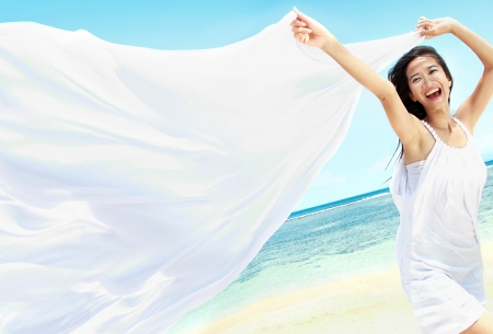 Reizen en Vakantie. Vrijheid Concept. Mooi Meisje Met Witte Sjaal op het strand genieten van de zomer. Stockfoto