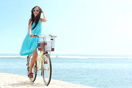 the carefree: carefree woman having fun and smiling riding bicycle at the beach Stock Photo