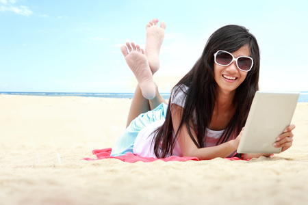 carefree woman uses touchpad tablet on the beach on holiday photo