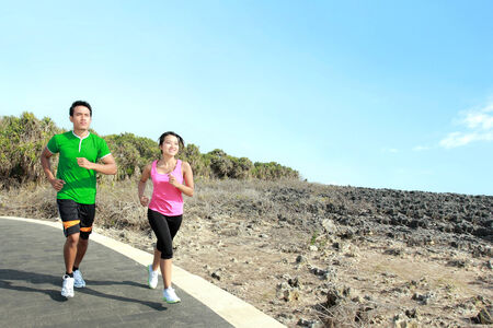 Sporty asian young couple running outside together on jogging track photo