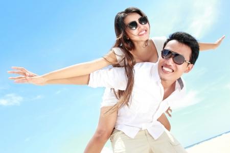 Man dragen het meisje op zijn rug plezier samen op het strand Stockfoto