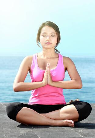 mind body soul: portrait of asian girl on the beach doing meditation