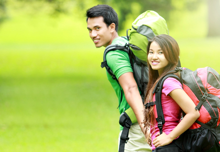 asian youth: camping concept. young man and woman with backpack camping together in the park