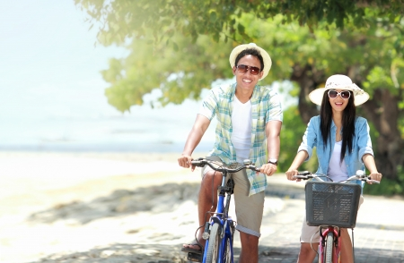 carefree couple having fun and smiling riding bicycle at the beach Stock Photo