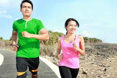 Sporty asian young couple jogging outside together on jogging track photo