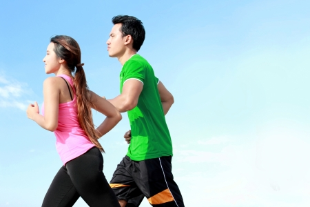 Sporty asian young couple running outside together