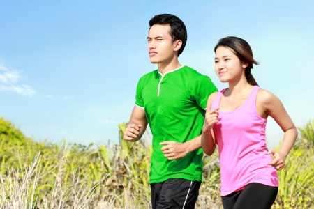 happy asian couple: Sporty asian young couple running outside together