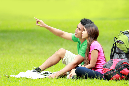 relaxing young couple with backpack camping together in the park photo