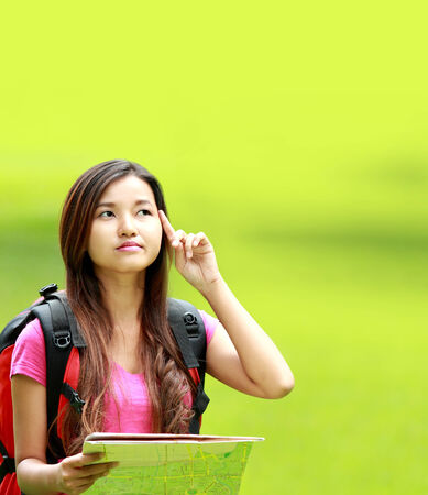 portrait of beautiful asian student wearing backpack thinking something in the park photo