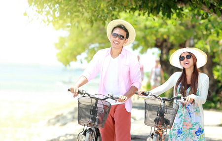 Portrait of happy asian young couple with bicycle on the beach having fun together photo