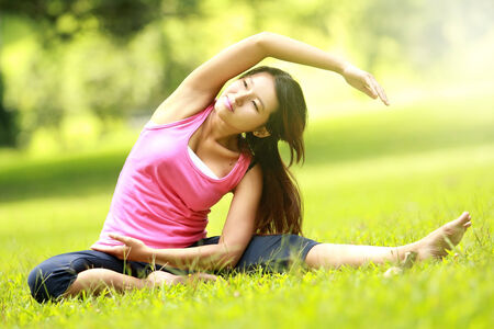 beautiful girl doing workout on grass in the morning photo