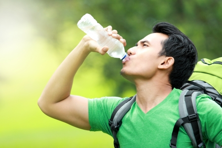 sediento: senderismo concepto. hombre sediento que tiene una rotura de beber una botella de agua
