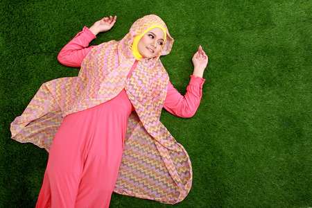 Portrait of young muslim woman wearing hijab lying on grass photo