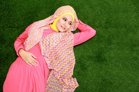 Portrait of young muslim girl wearing hijab lying on grass photo