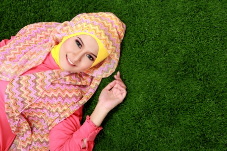 Portrait of young muslim girl wearing hijab lying on grass with copy space photo