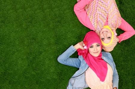 femmes muslim: Portrait de deux belles femme musulmane heureuse souriante allong� sur l'herbe, avec copie espace