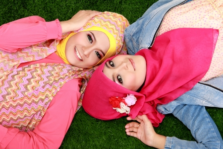 Portrait of close up two beautiful happy muslim woman lying on grass