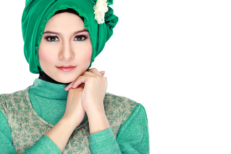 Fashion portrait of young beautiful muslim woman with green costume wearing hijab isolated on white background photo