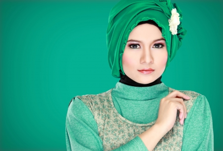 Fashion portrait of young beautiful muslim woman with green costume wearing hijab isolated on green background photo