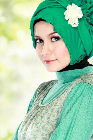 hijab: Fashion portrait of young beautiful muslim woman with green costume wearing hijab isolated on white background