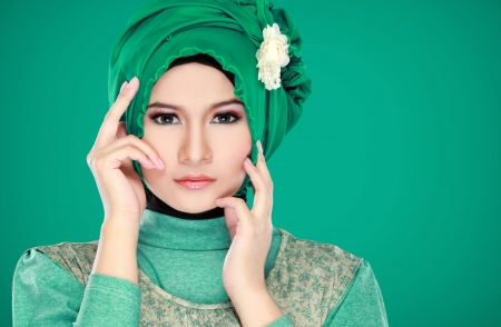 muslimah: Fashion portrait of young beautiful muslim woman with green costume wearing hijab isolated on green background