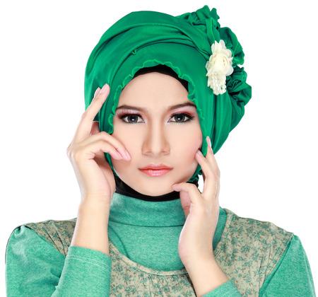白い背景で隔離のヒジャーブを着ている緑の衣装ファッションの若い美しいイスラム教徒の女性の肖像画