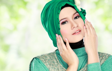 Fashion portrait of young beautiful muslim woman with green costume wearing hijab photo