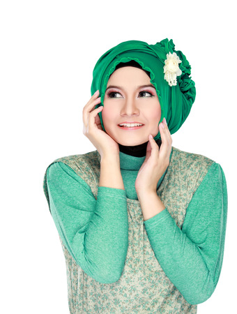 Fashion portrait of young happy beautiful muslim woman with green costume wearing hijab and looking up isolated on white background