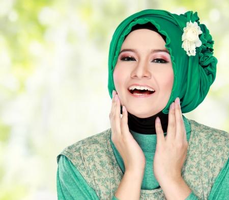 hijab: Fashion portrait of young happy beautiful muslim woman with green costume wearing hijab