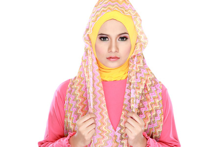 Fashion portrait of young beautiful muslim woman with pink costume wearing hijab isolated on white background photo