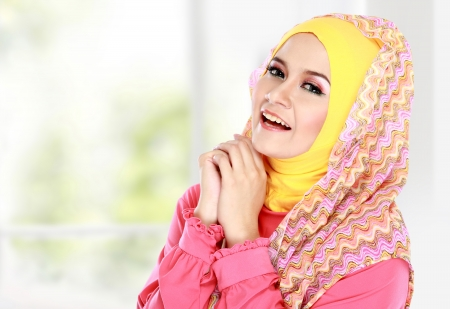 Fashion portrait of young happy beautiful muslim woman with pink costume wearing hijab photo