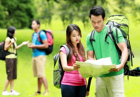 young man and woman with backpack holding map camping together in the park photo