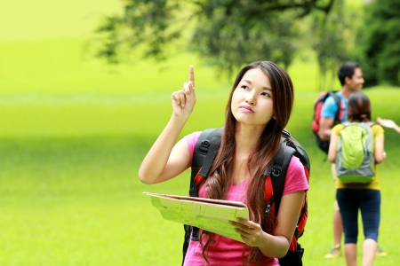 portrait of curious asian girl camping in the park pointing at something photo