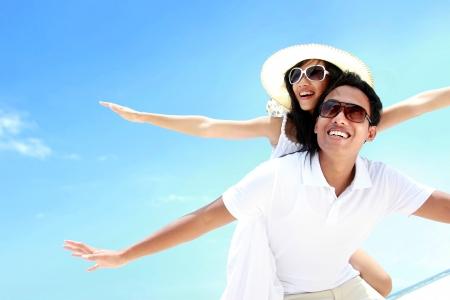 mujer alegre: Feliz pareja sonriente de verano incluirse junto con los brazos extendidos en playa hermosa