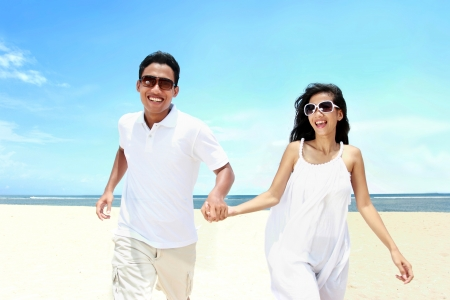 honeymoon couple: Portrait of beach couple in white dress running having fun laughing together Stock Photo