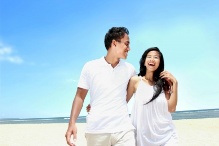 Portrait of beach couple in white dress having fun laughing together photo