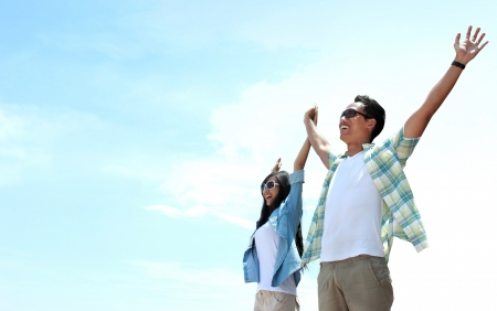 Portrait of asian young couple standing and raised their hands to the sky