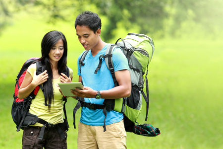 Portrait of happy couple going on a hike together looking at tablet pc in the countryside photo
