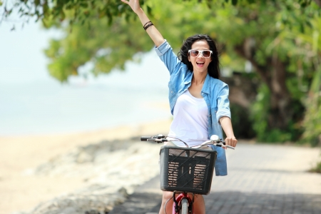 girl on bike: happy asian woman having fun and smiling riding bicycle at the beach