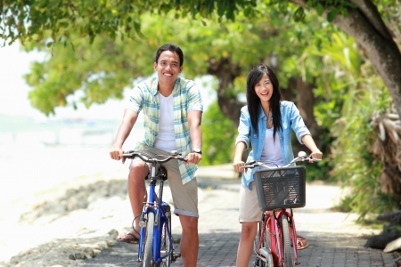 man and woman having fun outdoor riding bicycle together and smiling to the camera photo