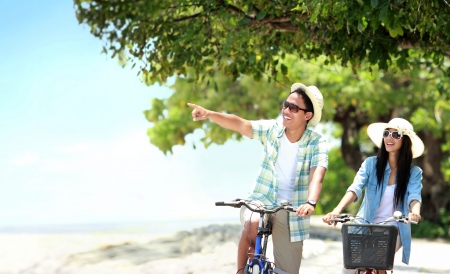 girl on bike: Portrait of carefree couple having fun and smiling riding bicycle at the beach Stock Photo