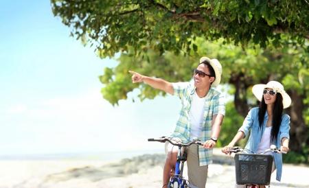 jovem: Retrato de casal despreocupado se divertindo e sorrindo andando de bicicleta na praia
