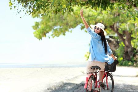 楽しんで屈託のない女性自転車に乗ると、ビーチで彼女の腕を上げて